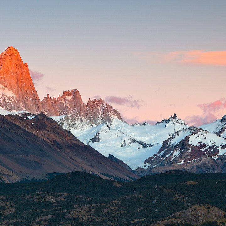 Fitz Roy range glowing red at sunrise seen from a lookout in El Chaltén